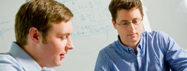 Andrew MacKinlay and Matthew Roberts working in front of a whiteboard