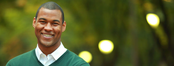 Michael Lemmons, WG'16, smiling in a green sweater in front of blurry trees and lights in the background.