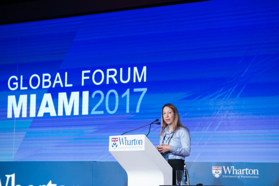 Sonia Rodriguez, president of the Wharton Alumni Club of South Florida, stands in front of a Wharton-branded podium with a screen reading Global Forum Miami 2017 behind her. She has long brown straight hair, a pleasant look on her face, and is wearing a light blue shirt and black bottoms.