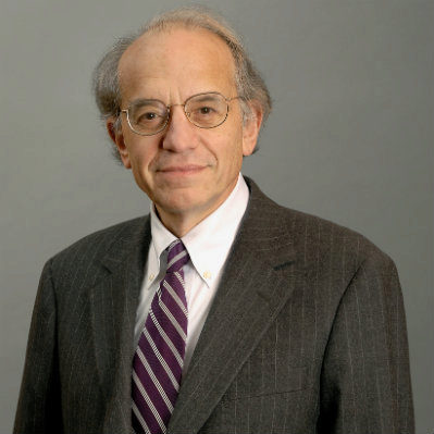 Prof. Jeremy Siegel standing in front of a grey background. He is wearing a grey suit and a striped burgundy tie