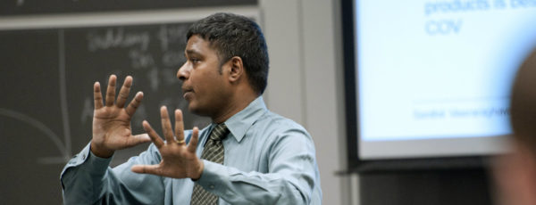 Senthil Veeraraghavan looks to the side, palms out, gesturing. He wears a blue shirt and green tie in front of a blackboard.