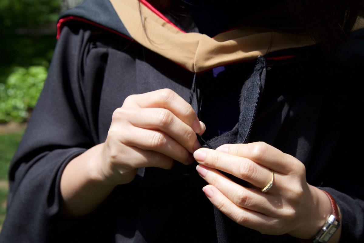 Student attaching Graduation hood