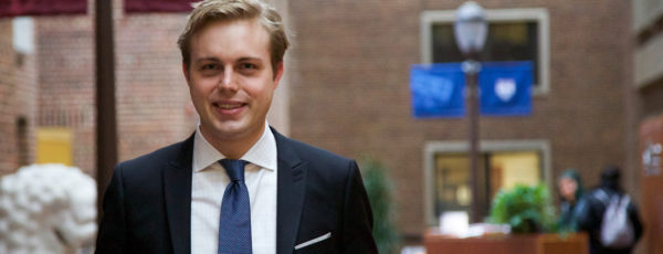 Closeup of Jon Hartley, WG'17, blonde in a navy suit, standing in the brick atrium of Steinberg-Dietrich Hall.