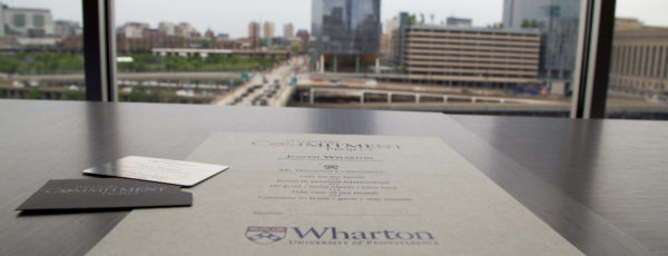 Closeup of a Wharton handout for the Commitment Project on a table, facing a window and a cityscape.