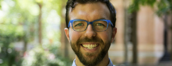 Headshot of Kyle Myers. He has short, brown hair and is wearing a blue shirt and glasses.