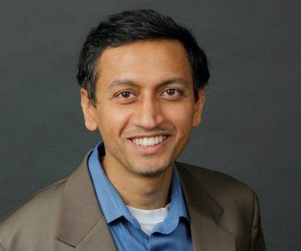 Kartik Hosanagar in front of a dark grey background. He has short, black hair and is wearing a grey blazer over a blue shirt.