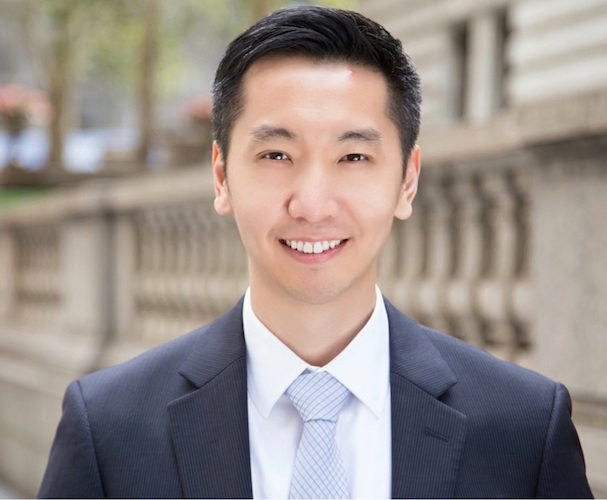Headshot of Robert Chen, WG'19, outdoors smiling in a blue suit, with a stone building in the background.