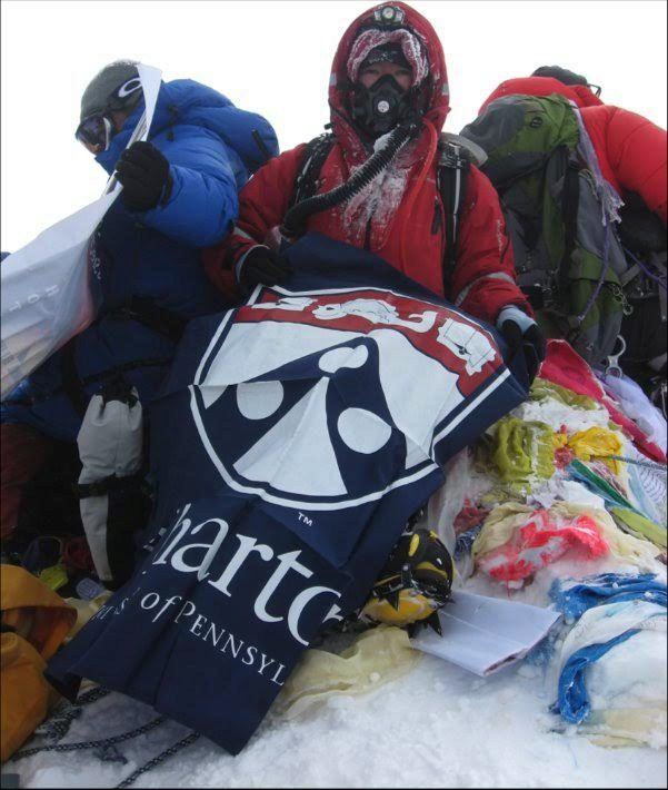Lei Wang atop Mt. Everest with a Wharton flag
