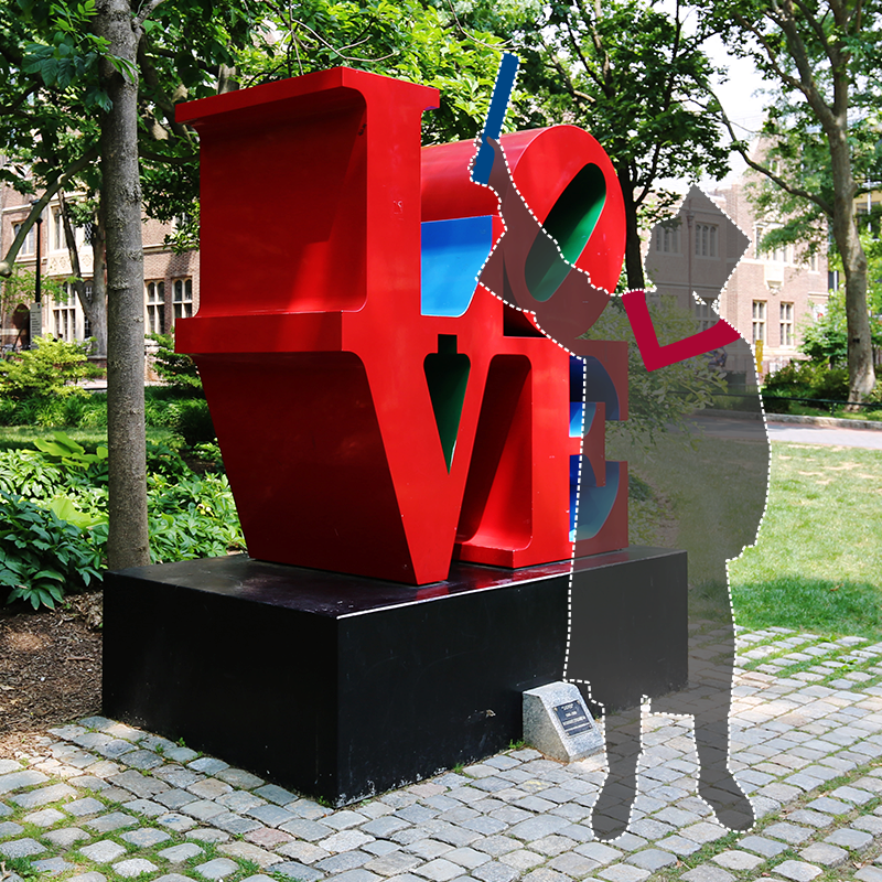 Graduate silhouette beside the Love sculpture on campus