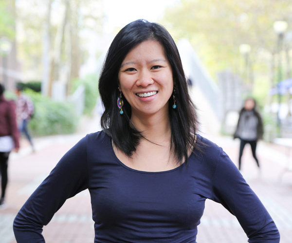 Dan Ping He, WG'19, smiling with colorful earrings and long black hair, her hands on her hips, trees and students behind her.
