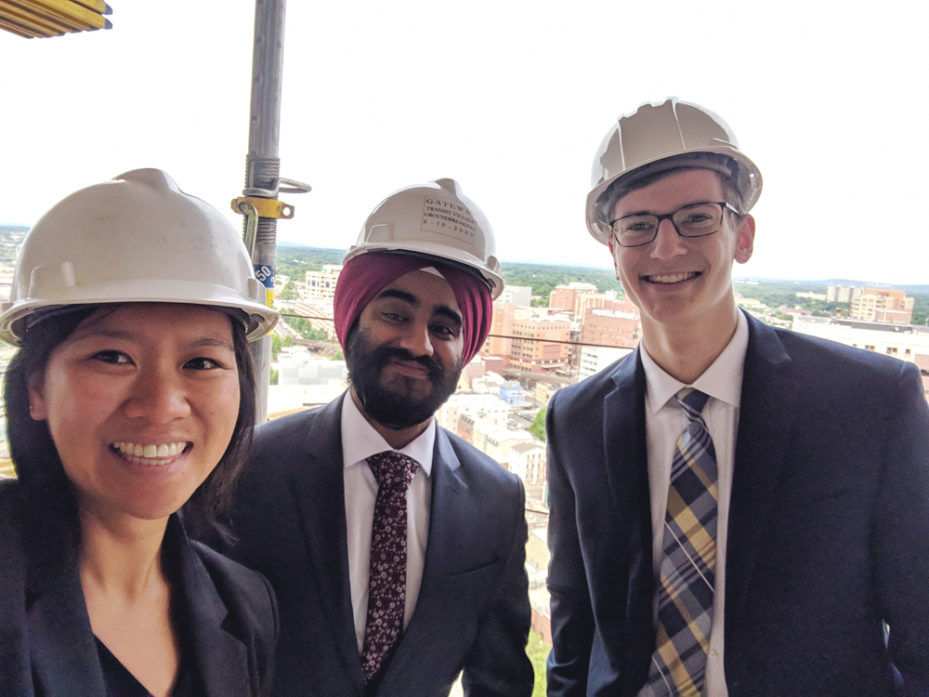Dan Ping He, WG'19, and two men smiling, wearing hard hats and suits, with a view of the city in the background far below.