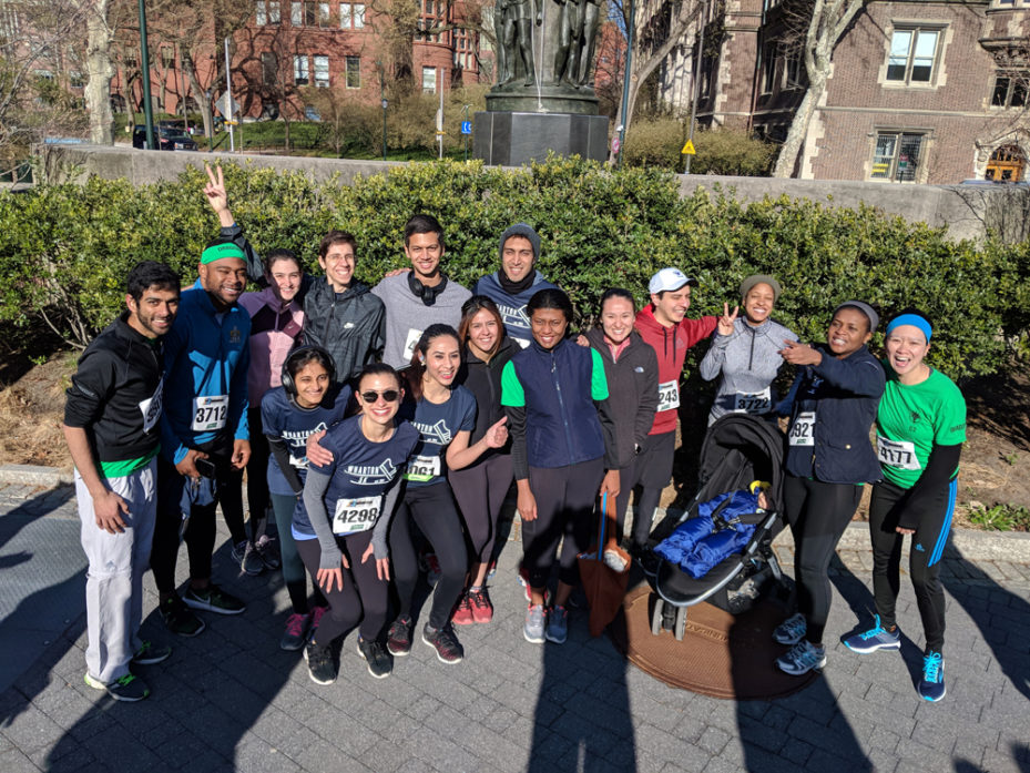 Dan Ping and a group of MBAs outside on a sunny day in exercise gear, standing in front of a row of bushes on campus.