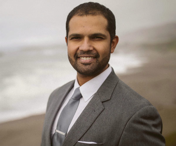 Professional photo of EMBA student Rajiv Srinivasan with a beach in the background. He is wearing a gray suit and smiling.