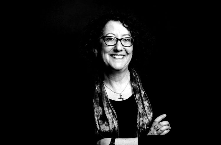 Black and white image of Suzanne Biegel with her arms crossed, smiling, and wearing glasses and a scarf.