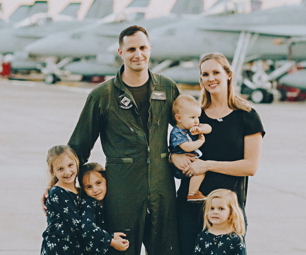 Chris Robinson in a flight suit with his wife and four young children on a tarmac with military planes
