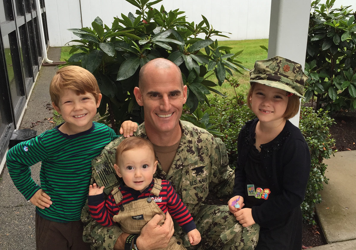 Craig Replogle holding a baby with two young children, one of whom is wearing his army cap