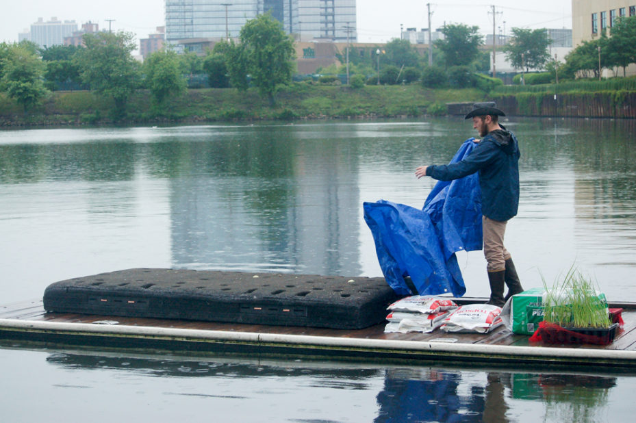 Josh unfurling a sheet as he stands on a canoe sailing down the river