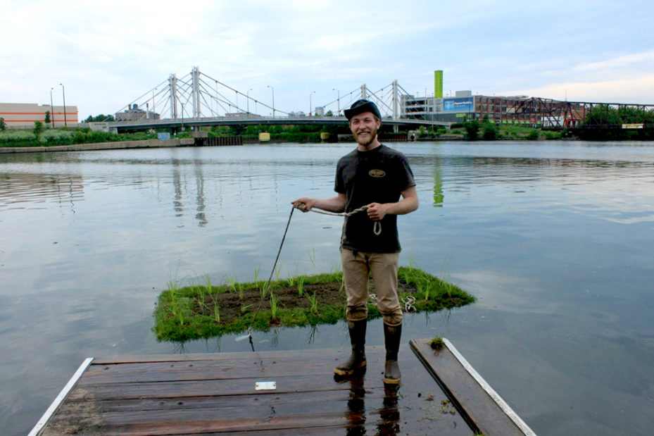 Josh pulling a small floating garden on the river