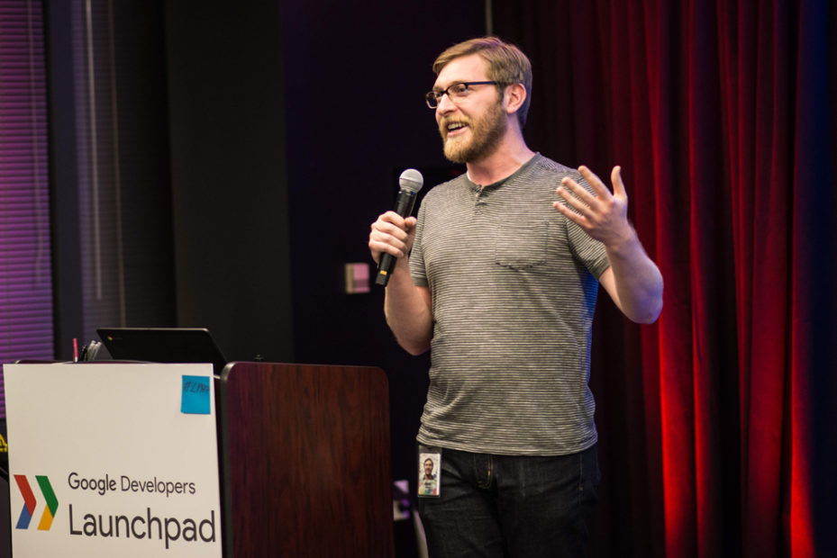 Josh with brown hair and beard in a gray shirt speaking to an audience at Google Launchpad in front of red curtains