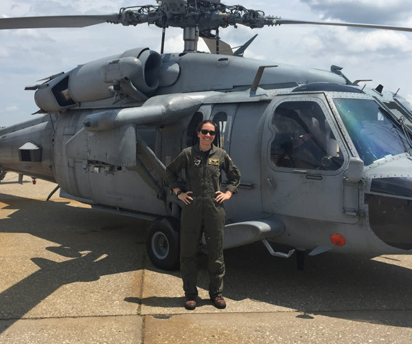 Sarah Bennett in a flight uniform in front of a military helicopter