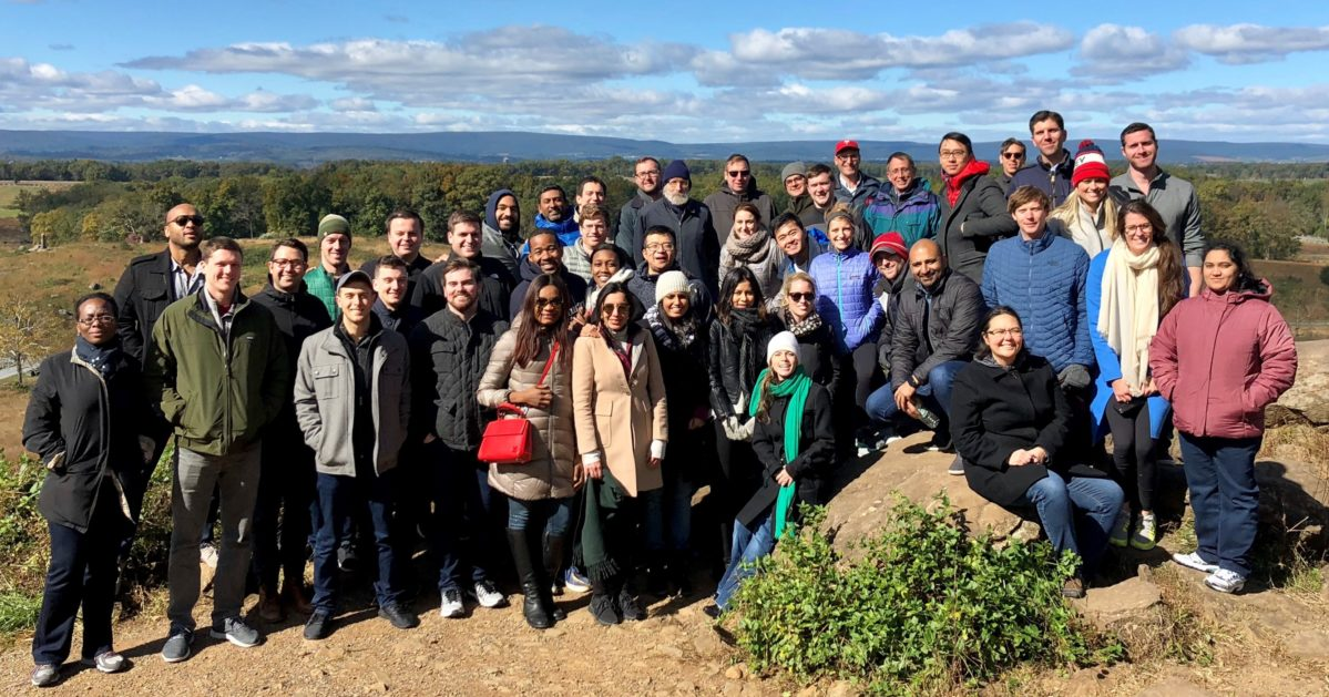 A large group of Wharton Executive MBA students stand on the Gettysburg battlefield on a cold day.