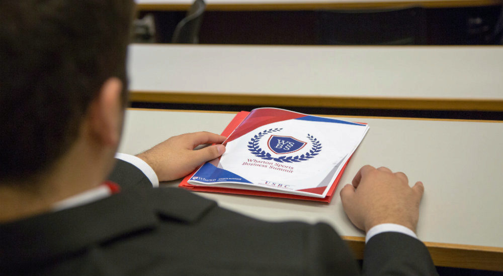 The back of a student in a suit. He sits at a desk with a red and blue Wharton Sports Business pamphlet in front of him.