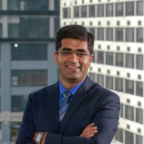 headshot of Ankit Girdhar standing with arms crossed and smiling in a suit with a blue shirt and tie
