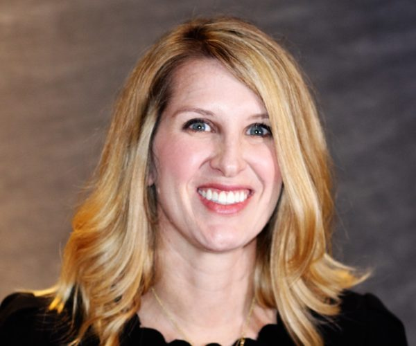 Headshot of Liz smiling with blond hair and a black shirt