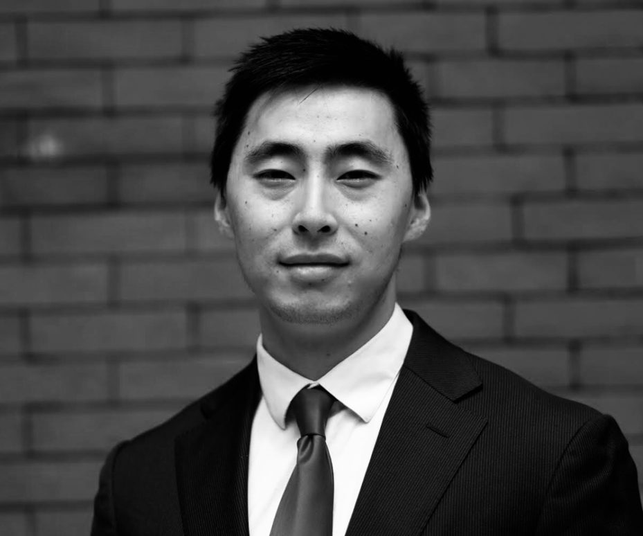 Black and white headshot of Yifan with cropped black hair in a suit with a brick wall behind him