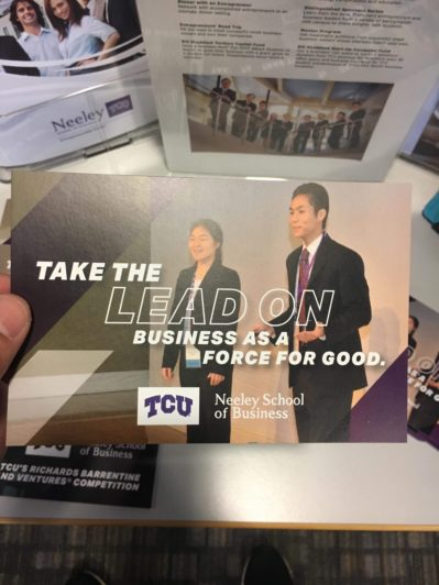A hand holding a brochure for the TCU Richards Barrentine Values and Ventures Competition, featuring Michael Wong giving a pitch.