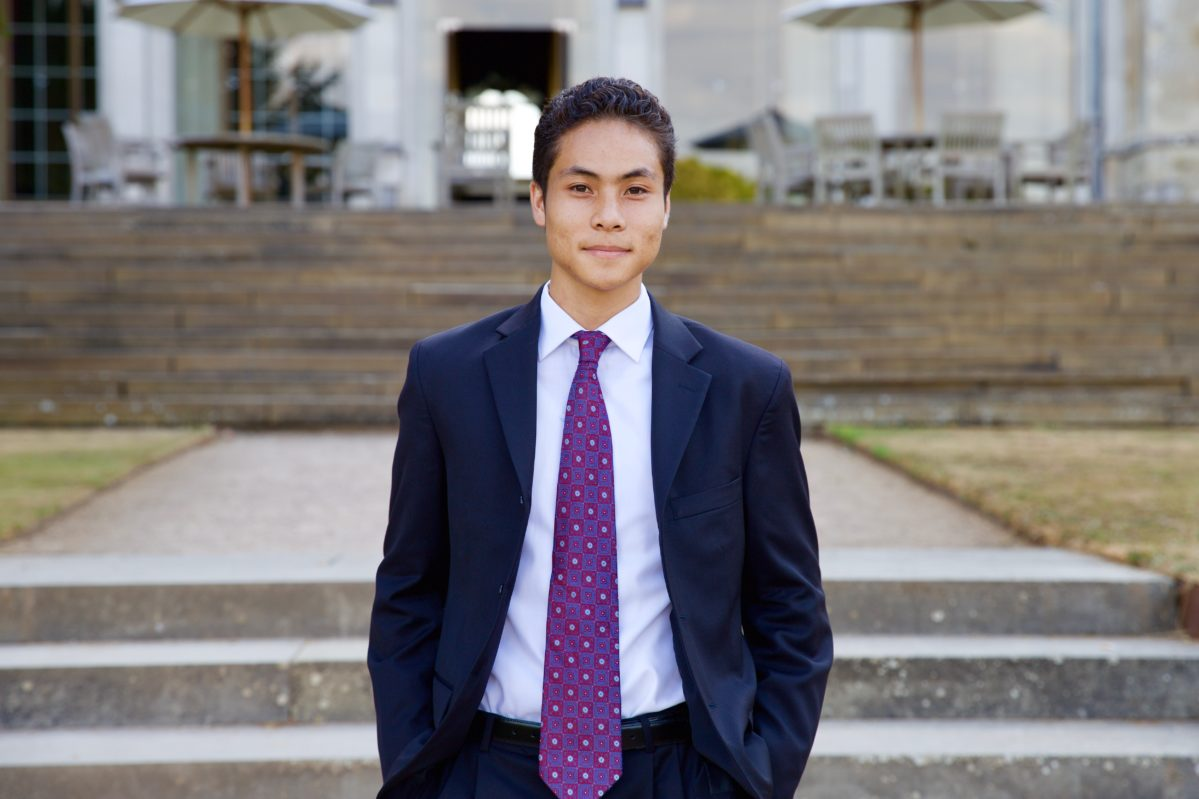 Headshot of Wharton undergrad Michael Wong standing outdoors, wearing a navy suite with a purple and red geometric printed tie.