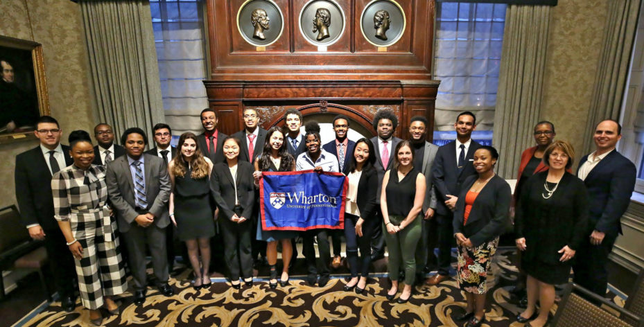 A group of students wear business casual in front of a large fireplace, holding up a blue and red Wharton banner.