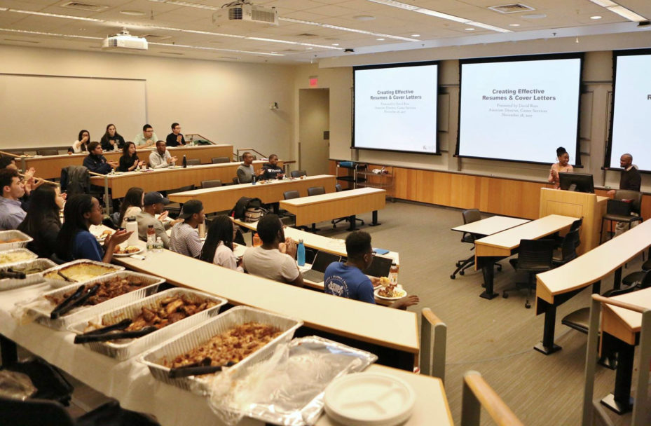 A classroom with three large screens, food trays in the back row, and students watching two speakers.