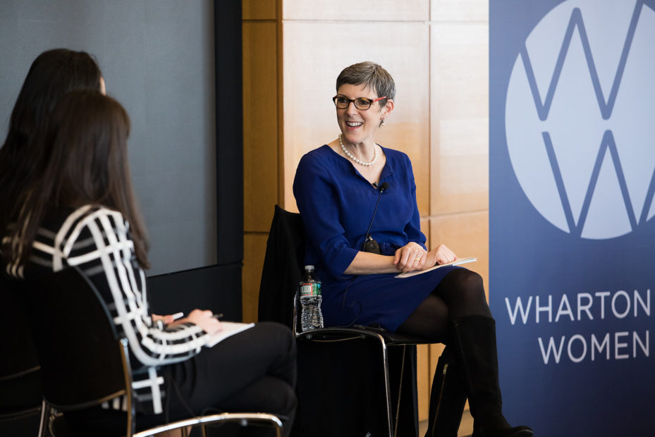 Marcus smiles. She wears a blue dress, glasses, black boots, and has short hair. There is a Wharton Women banner behind her.