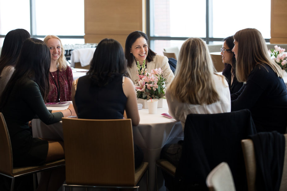 Eight women sit around a large table. They wear business casual and are smiling and conversing.