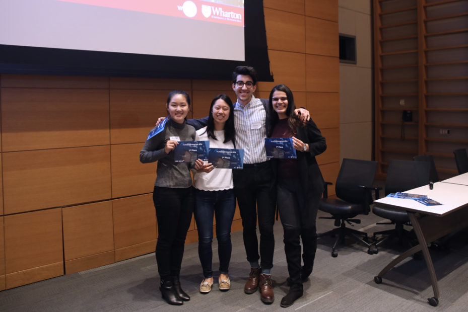 "Four students smile and hold blue awards that say ""First Place""."