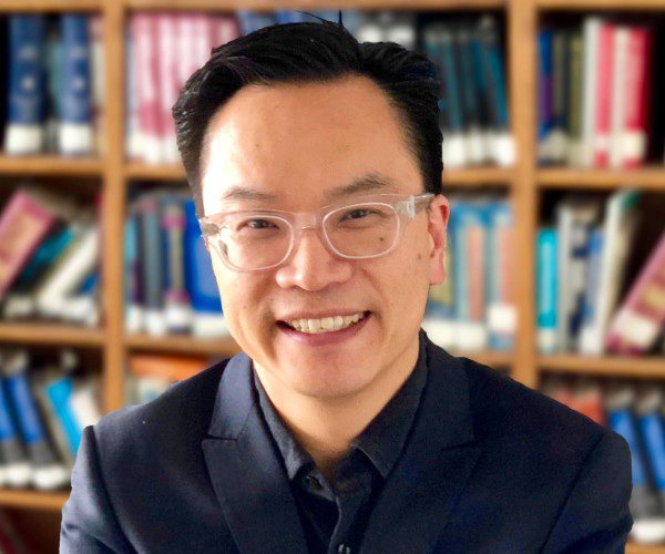 Dr. John Wong smiles into the camera for a headshot. The background is a full bookshelf.