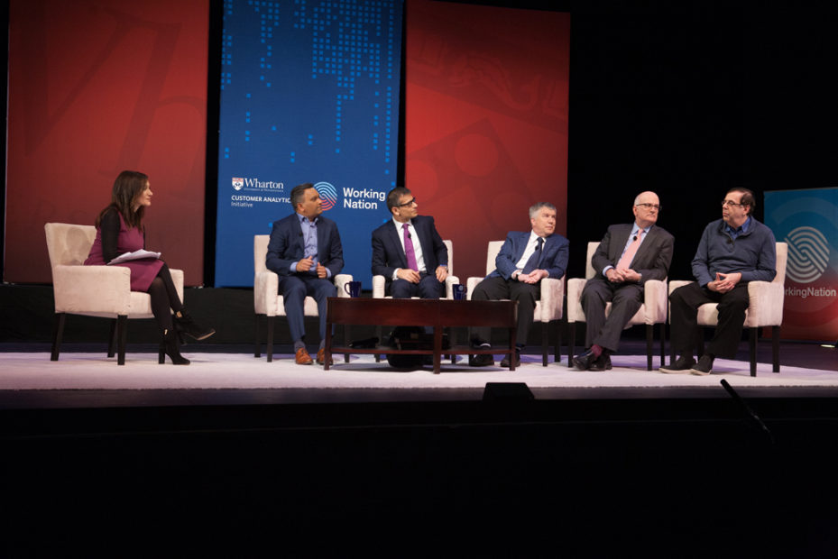 Five panelists sitting on stage with the moderator with large blue and red event banners behind them