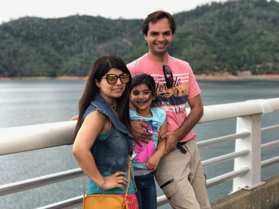 Swati leaning against a railing with her husband and daughter with a lake and mountains behind them