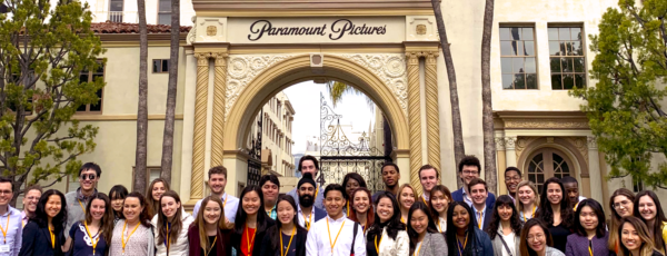 Students smile in front of a large yellow gate that reads: Paramount Pictures.
