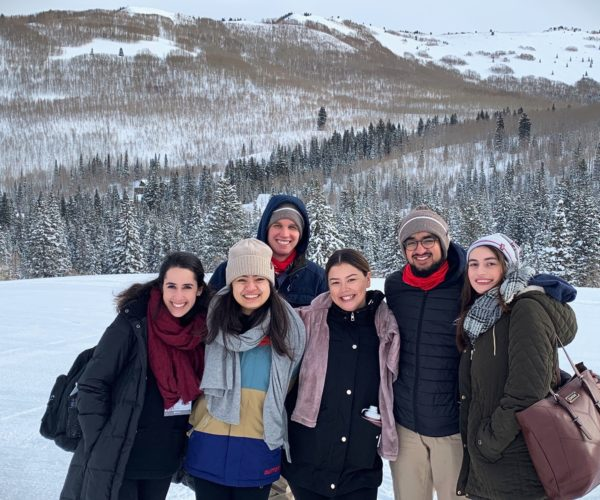 a group of students smiling outdoors in Utah with a backdrop of mountains and snow