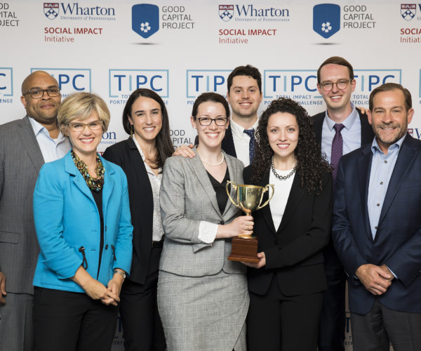 University of Vermont MBA students posing with TIPC judges in front of a step and repeat banner