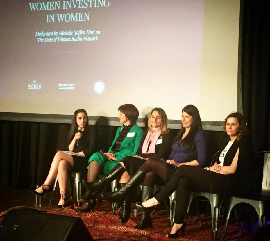 Michelle holding a microphone moderating a panel of 4 other women sitting on a stage