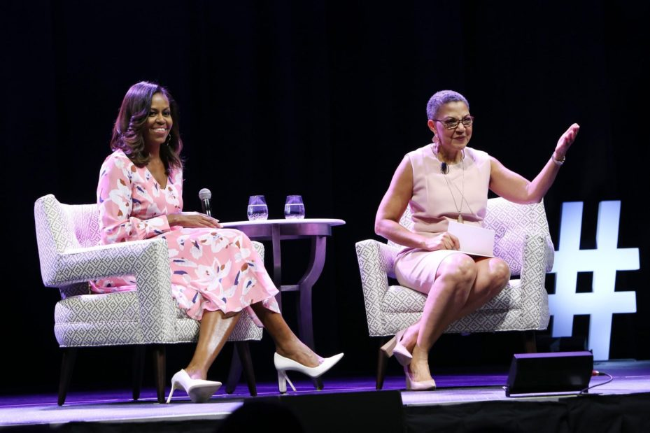 Michelle's perspective in the audience of an event featuring Michelle Obama, who is sitting on stage with another woman