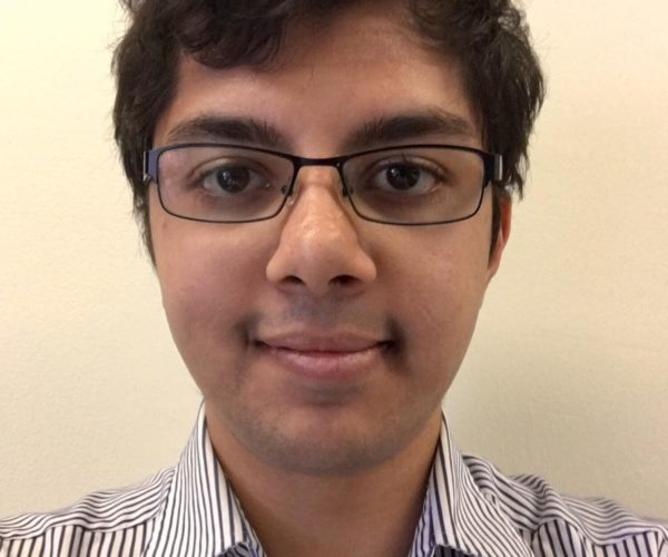 Rishabh headshot with short dark hair, black rimmed glasses, and a black and white striped button down shirt