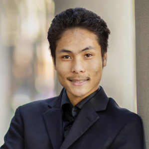 headshot of michael wong wearing a black blazer and black collared shirt