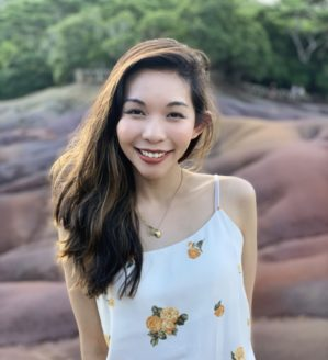 natalie au headshot wearing a white tank top with yellow flowers