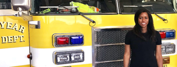 Shanel Fields standing in front of a yellow firetruck