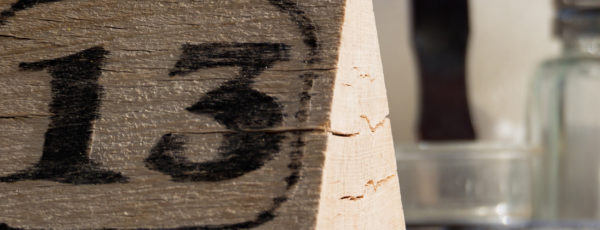 An image of the number thirteen on a woodblock next to a salt shaker.