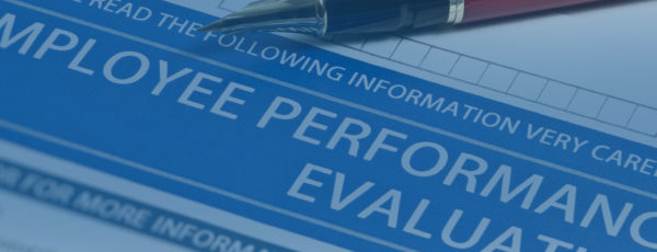 A blue tinted image of a paper with a pen. The paper reads: Employee Performance Evaluation